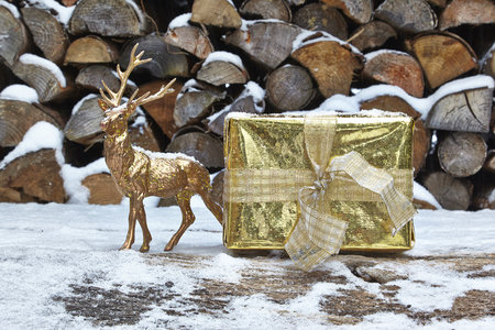 animal figurines: Christmas present and deer figurine in front of woodpile