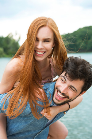 carrying girlfriend: Happy couple at lake, man carrying girlfriend piggyback Stock Photo