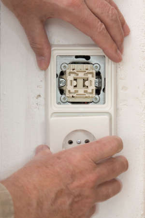 switch on the light: Interruptor de luz y enchufe en la pared en la mano