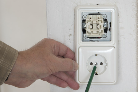 light socket: mano con un volt�metro, interruptor de la luz y enchufe