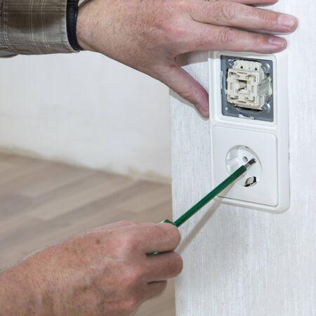 enchufe de luz: Renovación, la mano con comprobador de tensión, interruptor de la luz y la toma de corriente