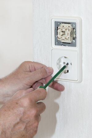 light switch: hand with voltage tester, light switch and plug socket Stock Photo