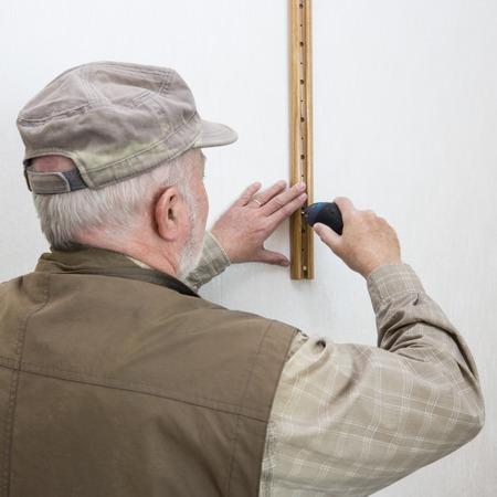 screwing: Senior man with drill, screwing on a shelf ledge