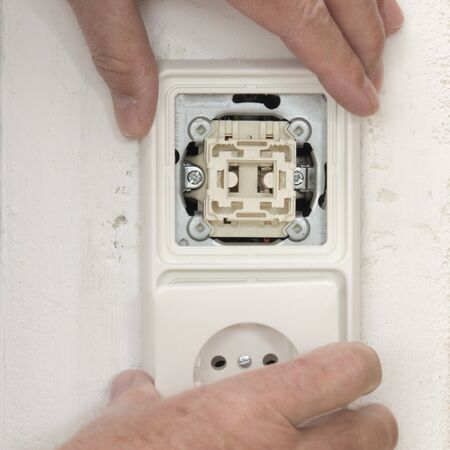 switch plug: Light switch and plug socket on wall in hand