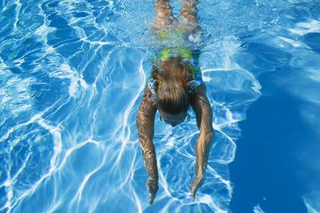 nadar: Piscina, mujer nadando bajo el agua Foto de archivo