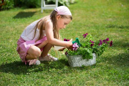 twee: Girl with spray bottle watering flowers in garden