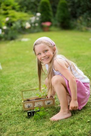 twee: Girl in garden planting herbs Stock Photo