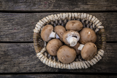 button mushroom: Organic brown champignons in basket on wood