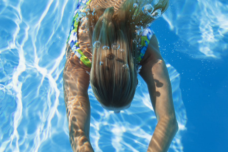 Swimming pool, woman swimming under water photo