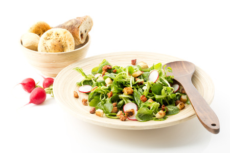 bacon bits: Lambs lettuce with bacon bits, croutons and red radish on plate