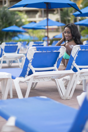 lounger: Beautiful young black woman sitting on sun lounger