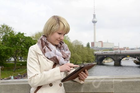 spree: Young woman with tablet at Spree river, Berlin, Germany