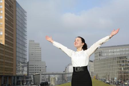 triumphing: Cheering business woman enjoying sun, Berlin,Gdermany