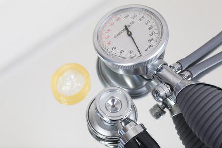blood pressure gauge: Blood pressure gauge and stethoscope and condom Stock Photo