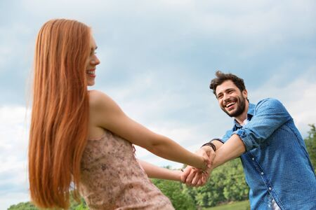 whirling: Happy young couple whirling around Stock Photo