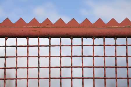 caged: Fence, grid of iron, spikes against blue sky