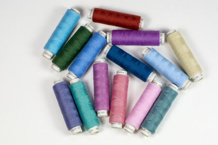 spermatophyte: Bobbins with colorful thread for tailoring on white background