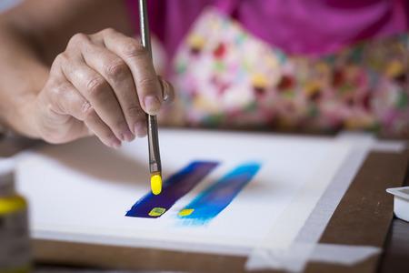 pintor: Cierre de la sección de la artista pintora - cepillo líder mano. Mujer que pinta un cuadro Foto de archivo