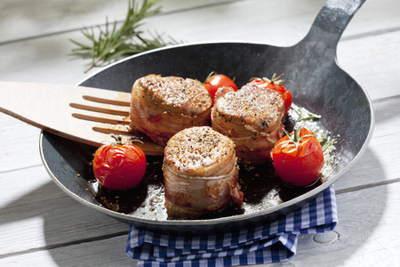 Bacon wrapped pork fillet with tomatoes in pan