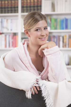 look pleased: Young blonde woman sitting in front of bookshelf