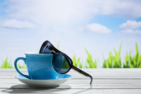 Koffiekop en zonnebril onder zonnige hemel