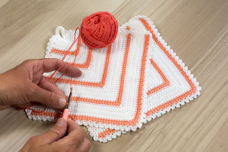 crocheted: Hands making crocheted pot  with wool and crocheting hook Stock Photo