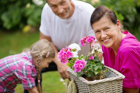 flower box: Family watering flowers in flower box Stock Photo