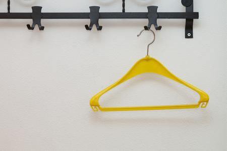 coat rack: Coat rack with yellow plastic hanger, copy space Stock Photo