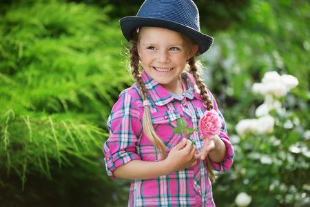 twee: Girl with blue hat in garden, holding flower