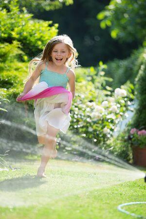 twee: Girl jumping through splashing water from garden hose