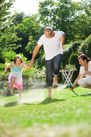 garden hose: Girl and grandparents playing and waterin garden Stock Photo
