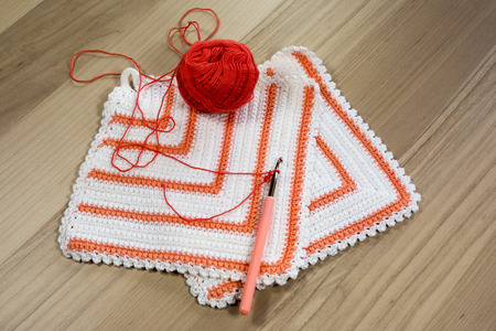 crocheted: Handmade crocheted pot  with wool and crocheting hook Stock Photo