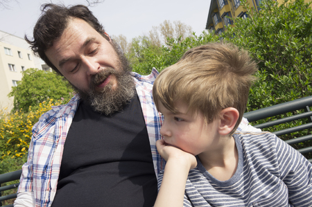 embarrassing: Father and son sitting on bench in park, Berlin, Germany