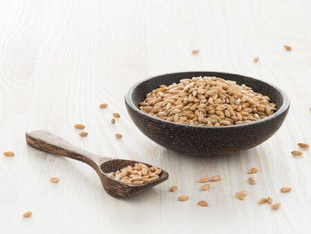 spelt: Spelt grains in wooden bowl on light background Stock Photo