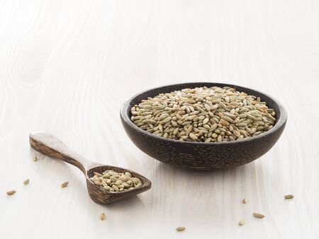secale: Rye grains in wooden bowl on light background