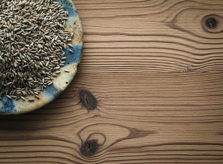 secale: Rye on plate against wooden background Stock Photo
