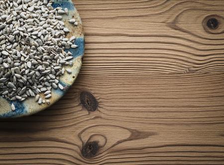 semillas de girasol: Las semillas de girasol en la placa contra el fondo de madera Foto de archivo