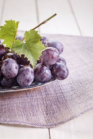 trivet: Blue grapes with leaves Stock Photo