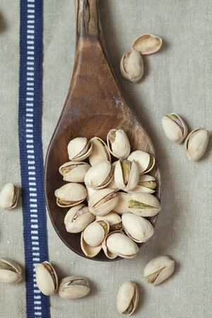 pistachios: Pistachios on wooden spoon