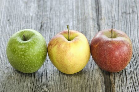 sort out: Green, yellow and red apple in a row on wood