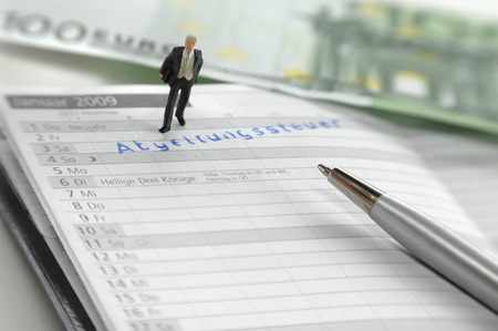 levy: Businessman figurine standing on pocket calendar, Deadline Abgeltungssteuer, close up