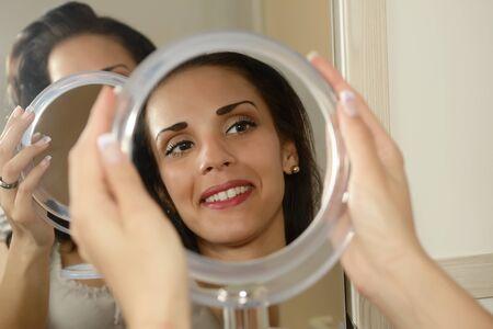 mirror?: Mujer joven que sonríe su imagen reflejada en el