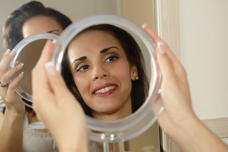 mirror image: Young woman smiling at her mirror image