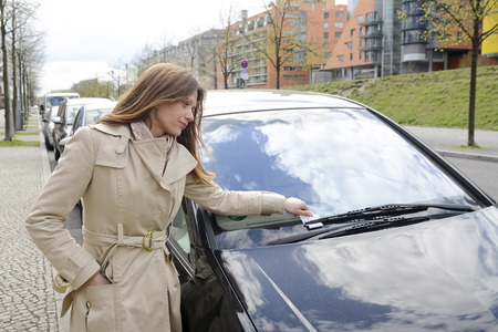 Young business woman finds parking violation ticket, Berlin, Germany
