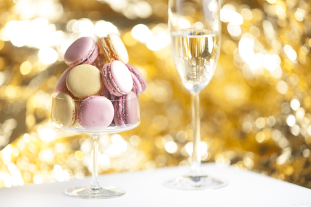 champain: Macarons in glass with a glass of champain, golden background