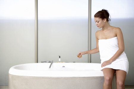 woman in bath: Woman preparing foam bath