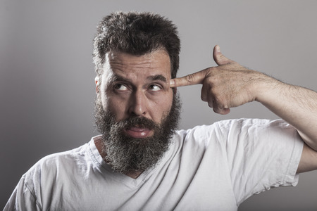 Portrait, man with full-beard, finger like a weapon on head