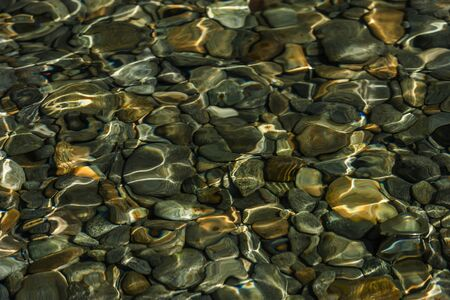su yüzeyi: Rippled water surface over pebbles
