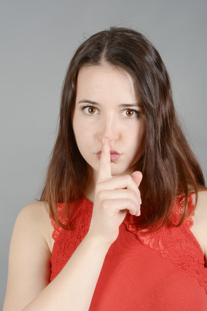 discretion: Young woman making hand gestures, finger on lips Stock Photo