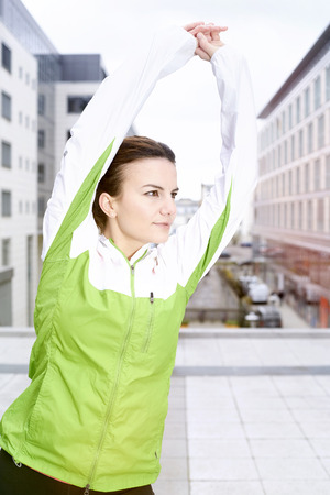 warming up: Young woman jogging in the city, warming up